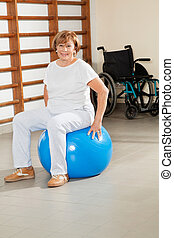 Senior Woman Sitting On Fitness Ball - Full length portrait...
