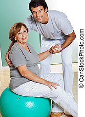 Therapist Helping Senior Woman Sitting On Fitness Ball