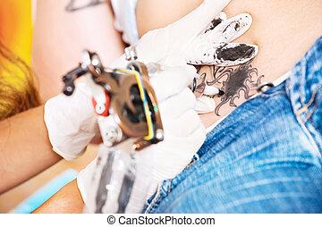 Tattoo art - hands of a tattoo artisan making art on belly