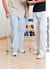 Man Holding Crutches Standing By Trainer