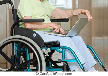Senior Woman Sitting In Wheelchair Using Laptop - Midsection...