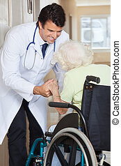 Doctor Assisting Senior Woman In Wheelchair - Happy young...
