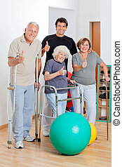Disabled Senior People With Trainer Showing Thumbs Up Sign -...