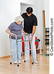 Trainer Assisting Senior Woman In Moving - Full length of a...