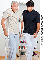 Trainer Helping Senior Man To Walk - Trainer helping senior...