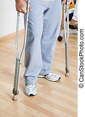 Woman Standing With Crutches - Low section of a woman...