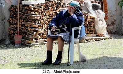 Grandmother cats - elder woman sitting in a rural courtyard...