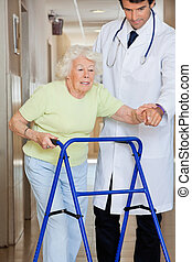 Doctor Showing Way To The Patient Using Walker