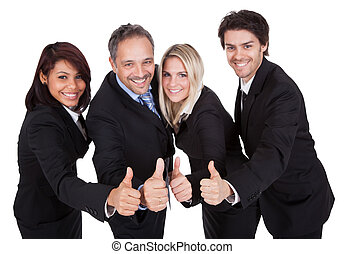 Happy business team celebrating a success with thumbs up on...