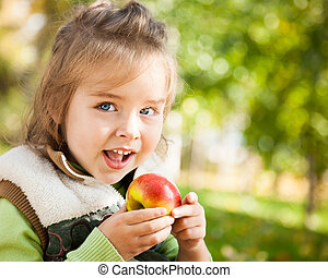 Child eating apple - Closeup portrait of happy child eating...