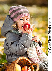 Child eating red apple - Smiling child eating red apple in...