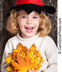 Happy laughing kid holding yellow maple leaves Halloween...