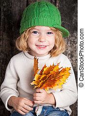 Kid with yellow maple leaves - Funny smiling kid holding...