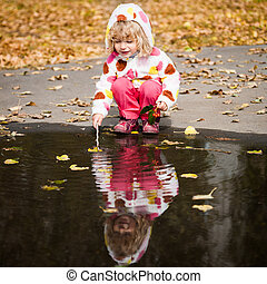 Child playing in puddle - Happy child playing in puddle in...