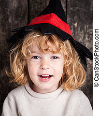 Funny kid in hand of witch - Happy laughing kid in hat of...