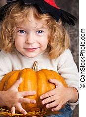 Child with big pumpkin - Happy smiling child in hat of witch...
