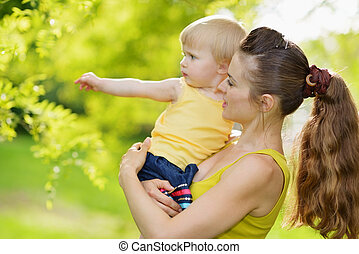 Outdoors portrait of mother and baby girl pointing in corner