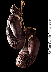 Old worn boxing gloves against a black background