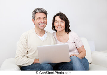 Mature couple using laptop at home - Mature couple shopping...