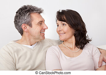 Portrait of happy mature couple sitting at home in the couch