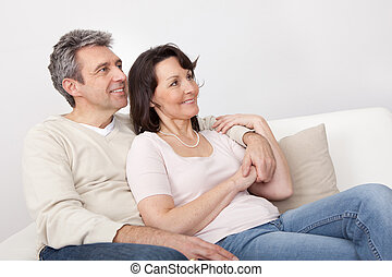 Happy mature couple dreaming about the future at home