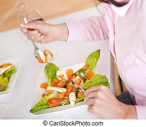 Woman eating salad at home