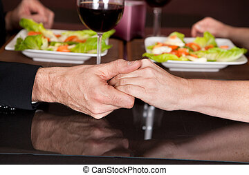 Touching hands at romantic dinner in restaurant - Mature...