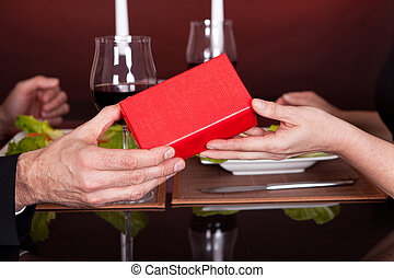 Man giving present to a woman in restaurant - Man giving...