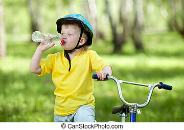 Cute child kid on bicycle and drinking  water fom bottle