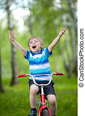 Portrait of a cute child boy on bicycle
