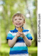 young boy eating a tasty ice cream outdoor