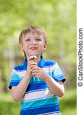 young smiling kid eating a tasty ice cream outdoor