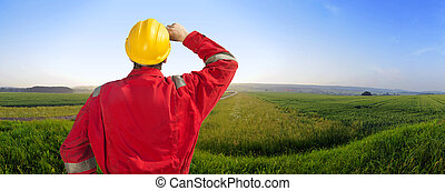 Engineering plans - Engineer in overalls and a hard hat in a...