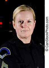 Police Officer - a female police officer in the night during...