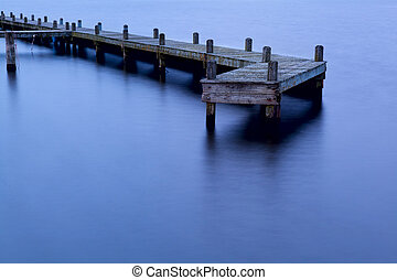 old wooden pier at dusk - old wooden pier in water at sunset...