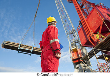 Construction operator looking at a crane carrying...
