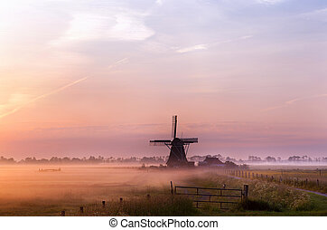 Dutch windmill in fog in the early morning - old Dutch...