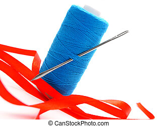 Threads, a needle and a satiny tape On a white background