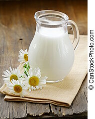 pitcher of milk on a wooden table wish daisy , rustic still...