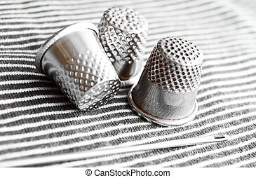 Needle and thimbles on a fabric. - Needle and thimbles on a...
