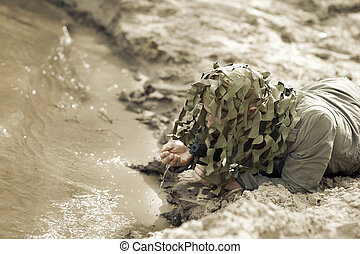 Military Camouflaged man with black handgu drink water from...