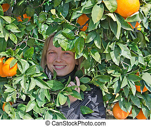 Girl at tree with ripe oranges