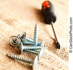 Screws and screw-driver on a fabric. - Screws and...