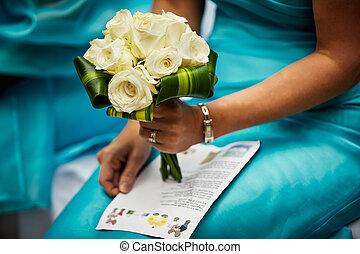 Bridesmaid holding the brides bouquet during the ceremony
