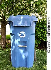 Recycle Bin under trees - A blue recyclying bin under a...