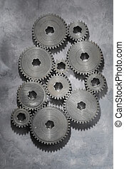 Old Cogs - Old metallic cog gear wheels on grey background.