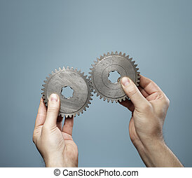 Matching Pair - A Man holding a matching pair of old cog...