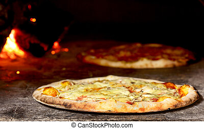 pizza in oven - delicious pizza baking in wood fired oven