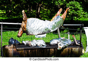 Whole roasted pig on a spit close up