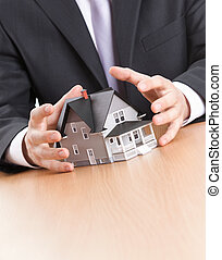 Business man hands around house architectural model